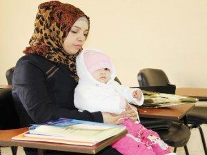 Suriyeli Pervin, kucağında 1 yaşındaki kızı ile okuma-yazma kursunda