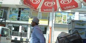 Eskici, güneşten şemsiye ve şapka ile korunuyor