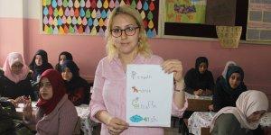 Çocuklara İngilizceyi resimlerle öğretiyor