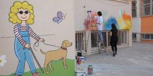 Fırça elde okul duvarlarını renklendiren öğretmenler